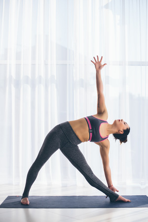 ushtrasana: Trikonasana. Beautiful yoga woman practice in a traning hall background. Yoga concept. Stock Photo
