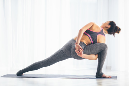 Parivritta parsvakonasana。トレーニング ホールの背景の美しいヨガ女性の練習。ヨガの概念。