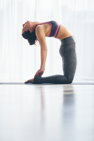 hasta: Ushtrasana. Beautiful yoga woman practice in a training hall background. Yoga concept. Stock Photo