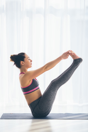 ushtrasana: Beautiful yoga woman practice in a training hall background. Yoga concept. Stock Photo