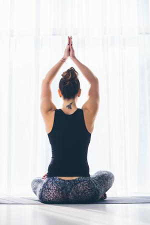 sukhasana: Sukhasana. Beautiful yoga woman practice in a training hall background. Yoga concept.