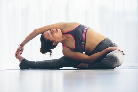 shirshasana: Djanu-shirasana. Beautiful yoga woman practice in a training hall background. Yoga concept.
