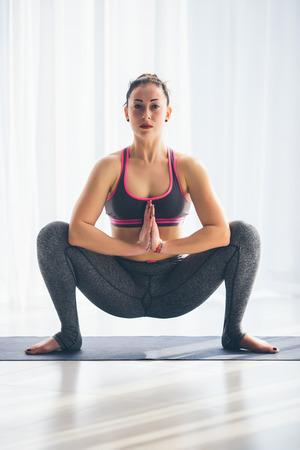 shirshasana: Kakasana. Beautiful yoga woman practice in a training hall background. Yoga concept. Stock Photo