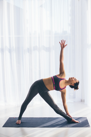 ushtrasana: Trikonasana. Beautiful yoga woman practice in a training hall background. Yoga concept.