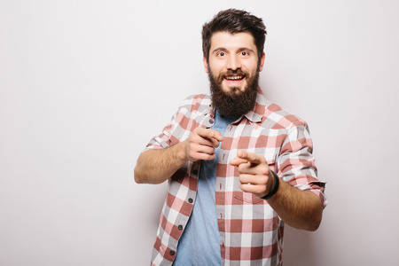 convinced: Handsome young man with beard demonstrate  invisible product presentation or advertising  pointed with hands while standing against white background