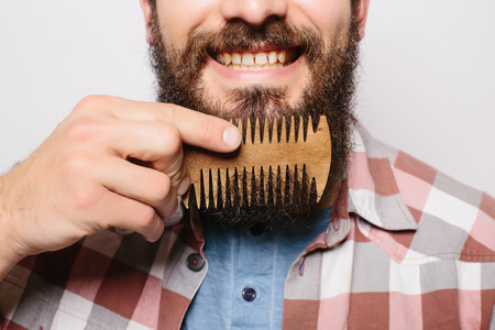 Handsome caucasian man close up with funny mustache comb beard and smile against white background