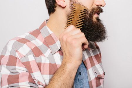 comb hair: Side portrait of handsome caucasian man with funny mustache smile and comb his big against white background.
