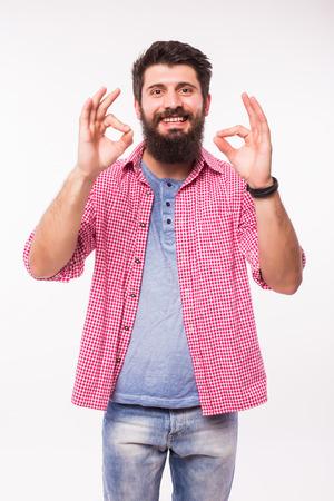 spaniard: Portrait of a happy hipster man with beard showing ok sign with fingers over whitebackground