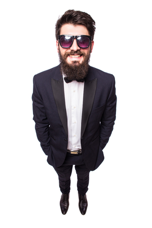 full height: Full height Confident young handsome man in sunglasses holding hands in pockets and looking at camera while standing against white background.