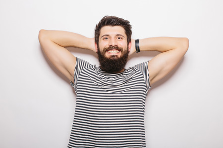 hands behind head: Handsome young man with beard holding hands behind head and smiling while standing against white background Stock Photo