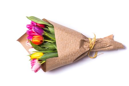 春のチューリップの花の花束は、白い背景で隔離紙に包まれました。