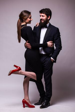 dress suit: Portrait of young couple in love posing dressed in classic clothes on grey backround. Man with beard in Suit, Woman in black Dress and red shoes. The concept of Spring holiday
