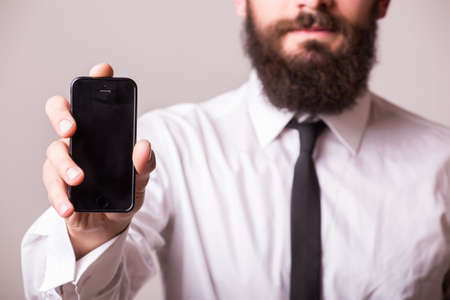 young bearded man pointet phone on white