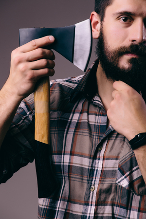 axe: Shaving with axe. Confident young bearded man carrying a big axe on shoulder and looking at camera while standing against dark background