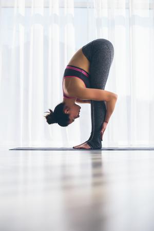 ardha: Padahastasana. Beautiful yoga woman practice in a training hall background. Yoga concept.
