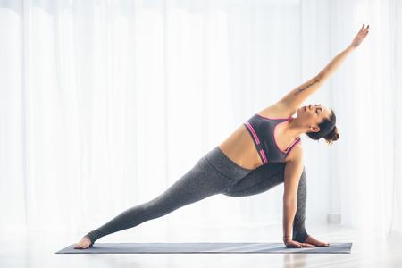 parsvakonasana: Utthita parsvakonasana. Beautiful yoga woman practice in a training hall background. Yoga concept.