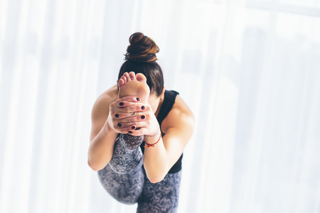 ushtrasana: Utthita hasta. Beautiful yoga woman practice in a training hall background. Yoga concept. Stock Photo