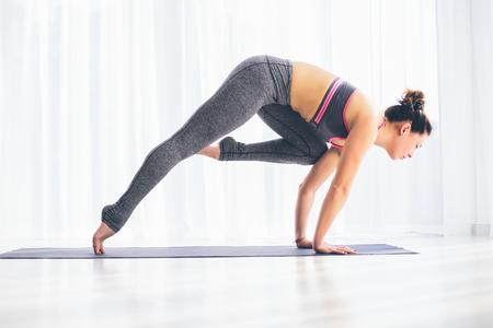 shirshasana: Ardha shirshasana. Beautiful yoga woman practice in a training hall background. Yoga concept.