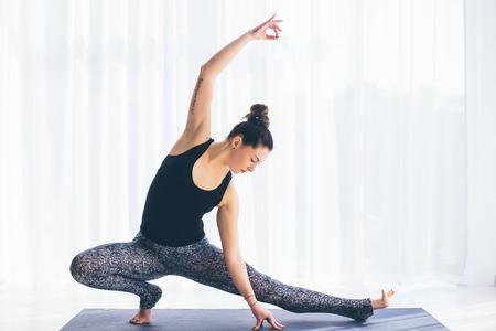 sukhasana: Virabadrasana. Beautiful yoga woman practice in a training hall background. Yoga concept.