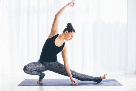 ardha: Virabadrasana. Beautiful yoga woman practice in a training hall background. Yoga concept.