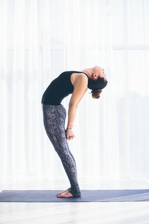 shirshasana: Urdhva hastasana. Beautiful yoga woman practice in a training hall background. Yoga concept.