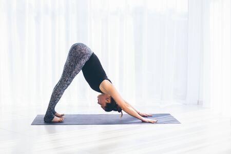 shirshasana: Adho mukha svanasana. Beautiful yoga woman practice in a training hall background. Yoga concept.