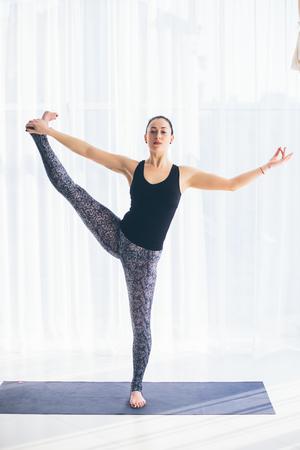 sukhasana: Utthita hasta. Beautiful yoga woman practice in a training hall background. Yoga concept. Stock Photo