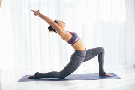 ushtrasana: Anjaneyasana. Beautiful yoga woman practice in a training hall background. Yoga concept.