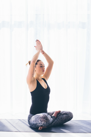 ushtrasana: Sukhasana. Beautiful yoga woman practice in a training hall background. Yoga concept.