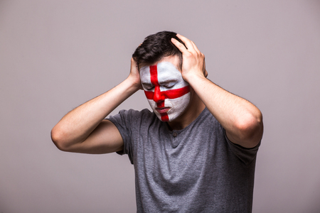 englishman: Unhappy and Failure of goal or lose game emotions of  Englishman football fan in game supporting of England national team on grey background. European football fans concept.