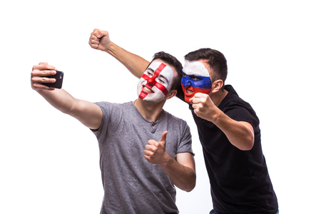 englishman: Selfie on phone of Englishman and Russian football fans in game supporting of national teams on white background. European football fans concept. Stock Photo