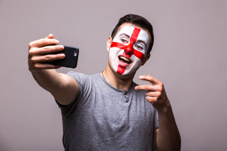englishman: Selfie on phone of Englishman football fans in game supporting of England national teams on grey background. European football fans concept. Stock Photo