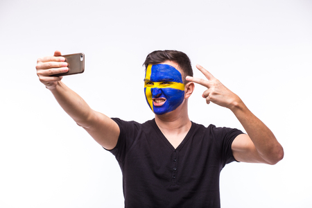 swede: Selfie on phone of Swede football fan in game supporting of Sweden national teams on white background. European football fans concept. Stock Photo