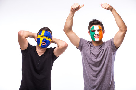 republic of ireland: Sweden vs Republic of Ireland. Football fans of national teams demonstrate emotions: Sweden lose, Republic of Ireland win. European football fans concept. Stock Photo