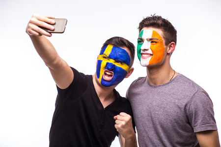 republic of ireland: Sweden vs Republic of Ireland football fans take selfie photo with phone on white background. European football fans concept. Stock Photo