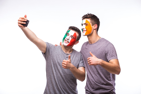 republic of ireland: Italy vs Republic of Ireland football fans take selfie photo with phone on white background. European football fans concept. Stock Photo