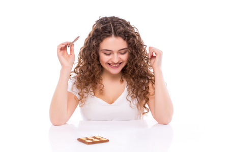 no food: Curly young woman with plate of  milk chocolate at table. Concept of diet.
