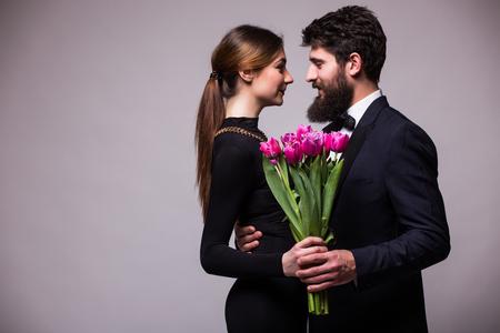 sweet couple: Young sweet couple with bucket of tulips on grey background Stock Photo