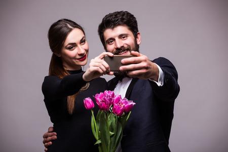fiestas electronicas: dulce pareja joven con el cubo de tulipanes tomar autofoto de tel�fono en el fondo gris