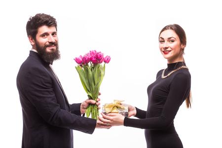dar un regalo: hombre joven da un regalo para su novia y tulipanes compartimiento en el fondo blanco