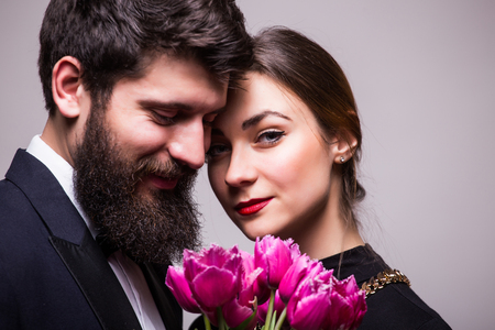 lila: Portrait of young couple with lila tulips on grey background