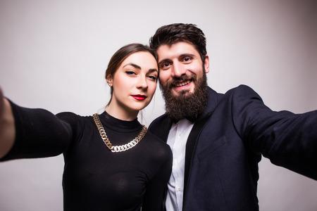 fiestas electronicas: Joven pareja toma autofoto de las manos sobre fondo gris Foto de archivo