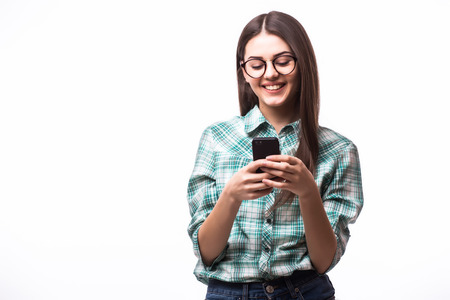 Attractive hipster girl wearing glasses and using her smartphone for texting