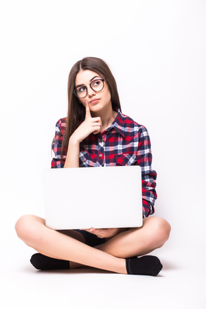 homeoffice: young woman working on her laptop, sitting on the floor over sparse white background