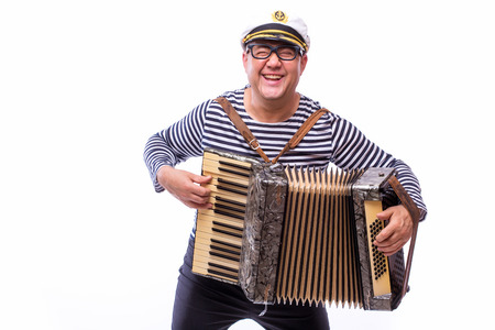 Sailor showman singer with musical instruments drum and accordion on white back Stock fotó