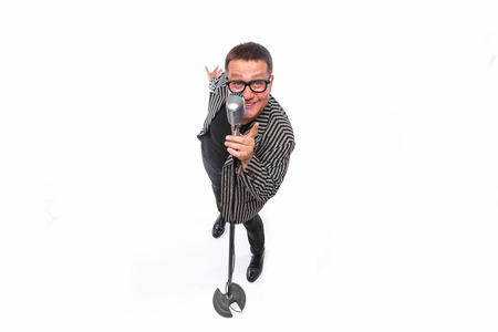 the showman: Middle age artist, showman singing in microphone on white from above. Stock Photo