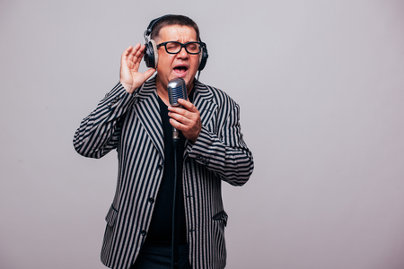 Singer sing on microphone on grey background Stock Photo