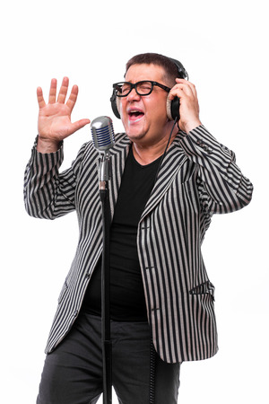 the showman: Showman concept. Singer listening music and sing in microphone on white background