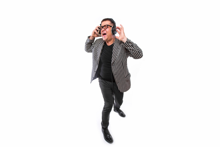 the showman: Showman concept. Middle age man listen music on headphones and sing song on white Stock Photo