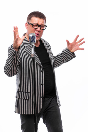 the showman: Portrait of middle age singer and showman singing on microphone